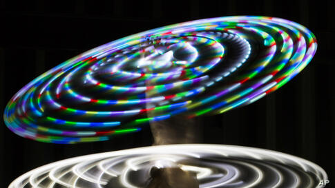 Canadian hooper Rebecca Halls performs with illuminated hula hoops at the Hula Hoop Festival Hoopurbia 2014 in Berlin, Germany.