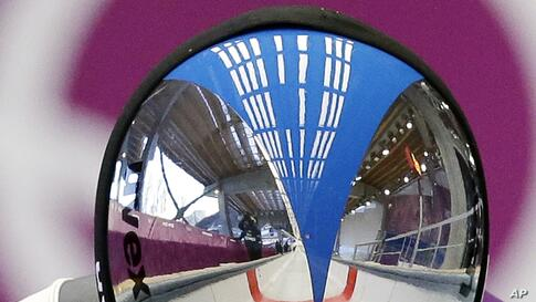 Armin Zoeggeler of Italy has his feet and the track reflected in his helmet as he starts a run during a training session for the men's singles luge at the 2014 Winter Olympics, in Krasnaya Polyana, Russia.