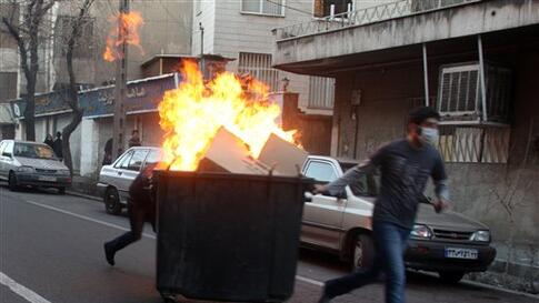This photo, taken by an individual not employed by the Associated Press and obtained by the AP outside Iran shows Iranian protestors moving a garbage can which is set on fire, during an anti-government protest in Tehran, Iran, Monday, Feb. 14, 2011. Eyewi