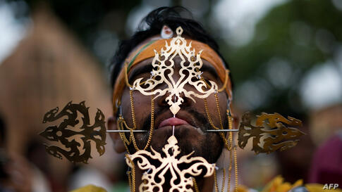 A Hindu devotee's tongue is pierced before making his way towards the Hill Top Murugan temple during the colorful annual Thaipusam festival, one of the world's most extreme displays of religious devotion, in Georgetown on the Malaysian island of Penang.