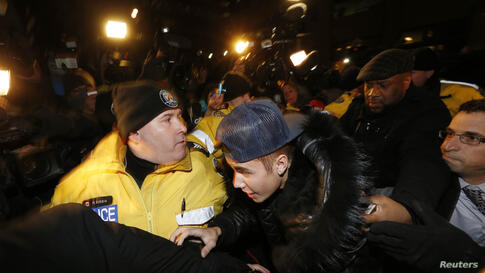 Pop singer Justin Bieber arrives at a police station in Toronto, Canada, Jan. 29, 2014. Bieber was mobbed by screaming fans and journalists as he entered a Toronto police station on Wednesday following reports he will be charged with assault over an in...