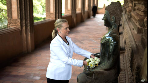 Clinton places flowers at a statue as she toured the Ho Phra Keo Temple, in Vientiane, Laos, July 11.