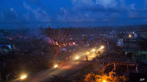 Typhoon Haiyan survivors ride motorbikes through the ruins of the destroyed town of Guiuan, Philippines.