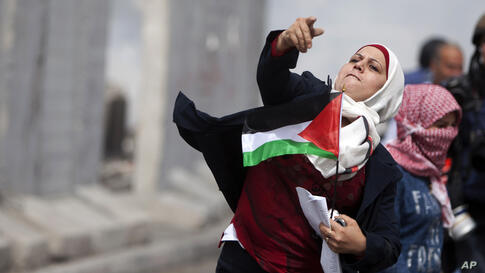 A Palestinian women throws a stone towards Israeli troops at Qalandia checkpoint between Jerusalem and the West Bank city of Ramallah. Palestinian women marked International Women's Day by marching to the checkpoint where clashes broke out with Israeli...