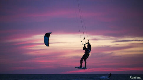 A man surfs with his kite in the Mediterranean sea at the southern Israeli city of Ashkelon, during the vacation of the Jewish holiday of Passover.