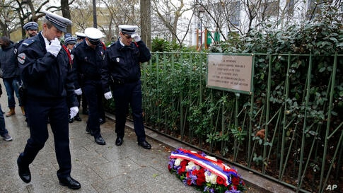 """Policemen walk past """"Je suis Ahmed,"""" or """"I am Ahmed,"""" spray painted on the sidewalk, in the red, white and blue colors of the French flag near a plaque commemorating late police officer Ahmed Merabet in Paris, France. President Francois Hollande honore..."""