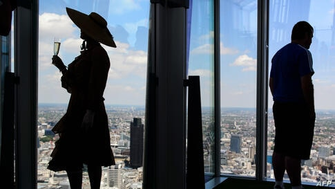 """A member of the Chap Olympiad group known as """"Auntie Maureen"""" (L) poses for photographs at the press launch of London's highest lawn in the Shard building, Britain."""