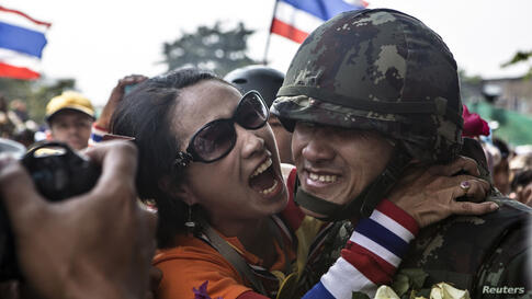 An anti-government protester hugs a Thai soldier, after some of the police personnel stationed in the Government house left the place following an agreement between the army and protesters, in Bangkok, Thailand.
