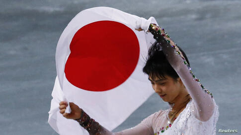 Japan's Yuzuru Hanyu carries the Japanese flag after winning gold in the men's free skating event at the 2014 Winter Olympics, February 14, 2014.