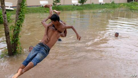 A man carries a boy as he leaps into flood waters on the outskirts of Phnom Penh, Cambodia.