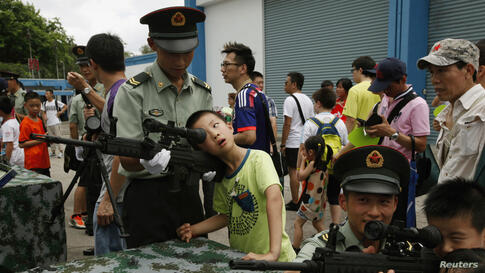 Young visitors peer through scopes of guns beside People's Liberation Army (PLA) Hong Kong garrison soldiers during an open day at Shek Kong airbase in Hong Kong.
