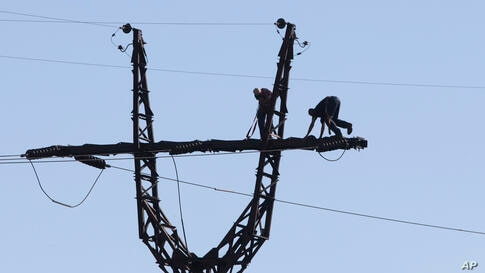 Workers repair an electricity power line damaged during shelling near a power station outside the city of Slovyansk, Donetsk Region, eastern Ukraine.
