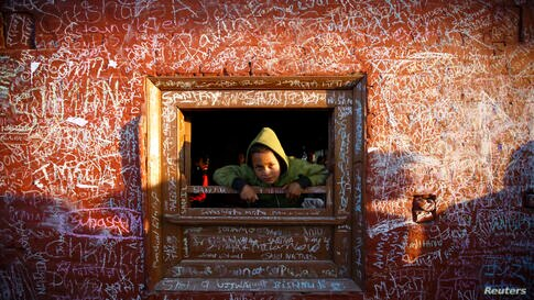 A boy looks through the window of the Saraswati temple, whose walls are filled with writings, during the Shreepanchami festival in Kathmandu, Nepal. Children are given their first writing and reading lessons at the temple during this festival in the be...
