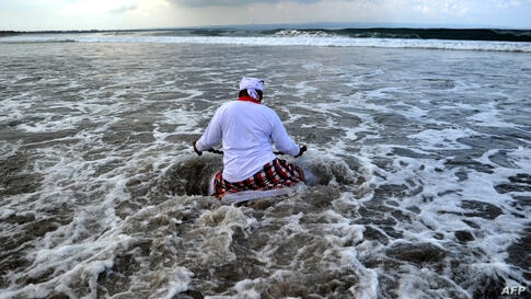 A Balinese man enters the water during a Melasti ceremony prayer at Petitenget beach near Denpasar on Bali island, Indonesia.