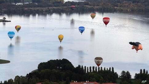 Hot air balloons float over Lake Burley Griffin during the Balloon Spectacular in Canberra, Australia.