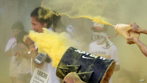 A runner gets pelted with color powders during the Color Run at the Dajia Riverside Park in Taipei, Taiwan.