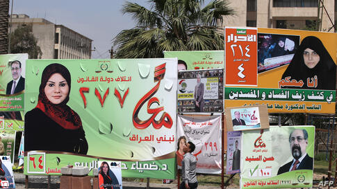 Iraqis walk past election campagin billboards in Kahramana Square in the capital Baghdad.