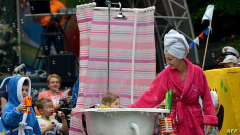 """A father (behind the shower curtain) pushes a self-made stroller designed to figure a bathtub during a """"stroller parade"""" contest, as part of the celebrations for the International Children's Day in Stavropol, southeastern Russia."""