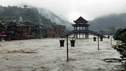 Street lamps are seen among floodwaters next to partially submerged buildings by an overflowing river at an ancient town as heavy rainfall hits Fenghuang county, Hunan province, China.