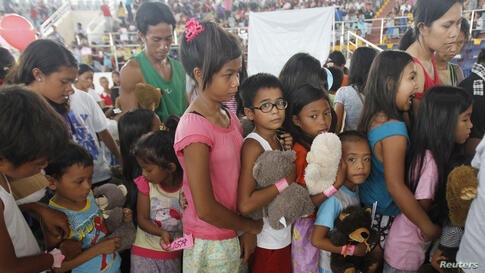 Survivors of Typhoon Haiyan line up during a gift-giving program inside an astrodome at Tacloban city, central Philippines.
