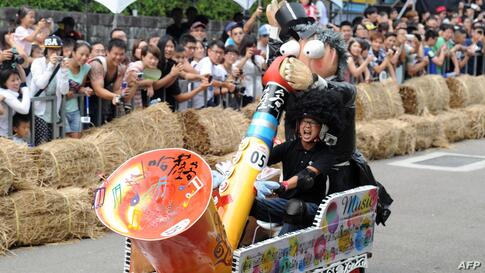A man operates a saxophone-shaped vehicle during a race organized by the Red Bull Soapbox Race at the Taipei University of the Arts. More then 50 vehicles take part in the 400-meter-long race.