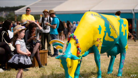 A child stands beside a plastic cow provided by a mobile telecoms company enabling free wifi for festival goers as revelers gather ahead of this weekend's Glastonbury Festival of Music and Performing Arts on Worthy Farm near Pilton in Somerset, south w...