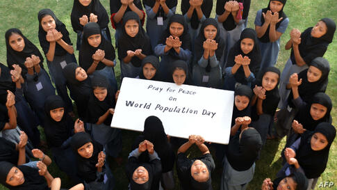 Muslim schoolgirls pose as they pray for 'World Peace' on 'World Population Day' in Jodhpur, India. World Population Day, which was established by the U.N. Development Program in 1989, is observed annually to raise awareness of global population issues.