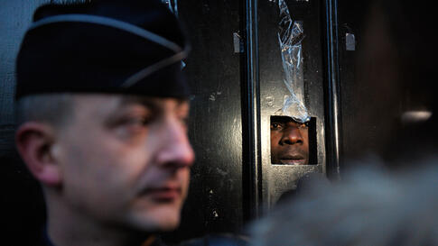 Dec. 27: A man speaks to journalists from inside the Ivory Coast embassy in Paris as police guard the entrance. (Philippe Wojazer/Reuters)