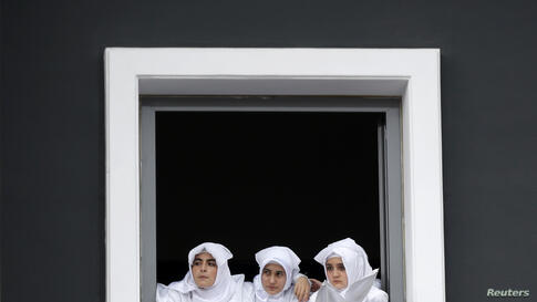 Turkish Shi'ite girls watch a re-enactment of the battle of Kerbala on a huge screen during an Ashura procession in Istanbul.
