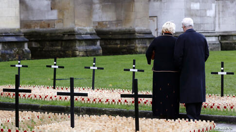 People pause among the crosses and poppies in the Field of Remembrance at Westminster Abbey in London, dedicated to those killed in the current conflict.