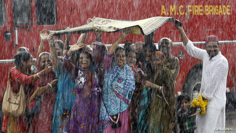 Relatives of Haj pilgrims wave in the rain, as they see off their relatives who are leaving Ahmedabad, India, for Mecca in Saudi Arabia to take part in the annual religious Haj pilgrimage.