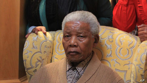Mandela poses for a photograph after receiving a torch to celebrate the African National Congress' centenary in his home village, Qunu, in rural eastern South Africa, May 30, 2012.
