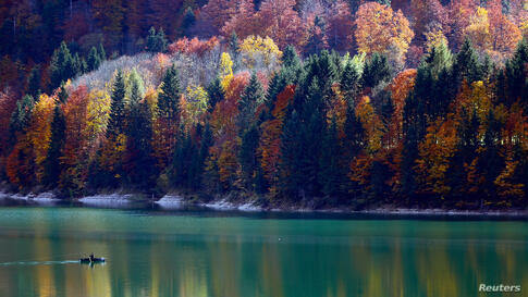 Autumnal trees are reflected in the water as a fisherman rows his boat during a sunny day at the Sylvenstein barrier lake in Germany.