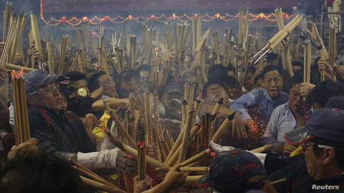 People rush to plant the first joss stick of the Chinese New Year at the stroke of midnight at a temple in Singapore.