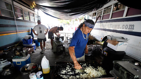 """Men prepare food in a protest camp called """"Romneyville,"""" August 28, 2012."""