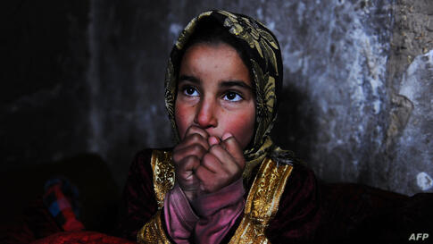 """An Afghan child warms herself near a traditional """"sandali"""" stove at her family's home in Herat."""