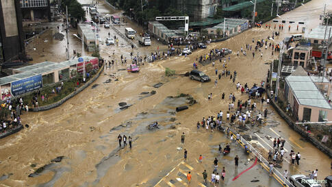 Vehicles come to a standstill at a flooded crossroad in Pingba, Guizhou province, China.