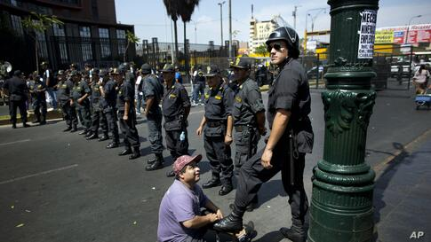 A shoe-shiner polishes the boots of a policeman who is standing guard during a protest organized by artisanal and small-scale gold miners in Lima, Peru, Mar. 24, 2014.