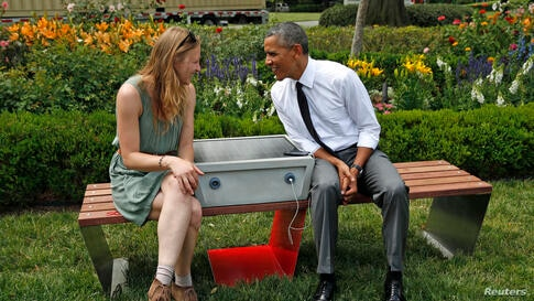"""U.S. President Barack Obama speaks with eco-friendly urban furniture designer Sandra Richter while hosting the first-ever White House """"Maker Faire"""" in Washington, D.C., June 18, 2014. The solar-powered bench allows people to charge their phones while r..."""