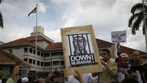 Protesters with slogans against Egyptian President Hosni Mubarak rally in front of U.S. Embassy in Kuala Lumpur, Malaysia, Friday, Feb. 4, 2011. More than 1,000 people protested outside the embassy, calling for Mubarak to step down.