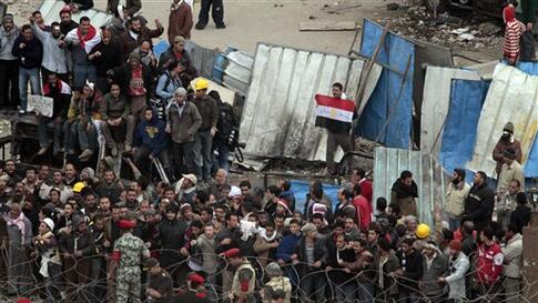 Egyptian army soldiers and tanks are positioned in front of anti-government demonstrators, to prevent clashes between Mubarak supporters, unseen, and anti-government protesters who shelter behind makeshift barricades, in Tahrir square, Cairo, Egypt,  Satu