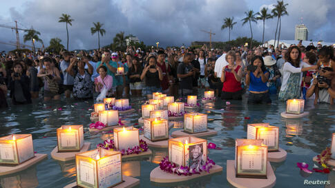 People take pictures of released floating lanterns dedicated to deceased loved ones during a ceremony marking remembrance and reflection, held by Shinnyo-en Buddhists honoring victims of war, famine, and natural disasters on Memorial Day, at Ala Moana ...