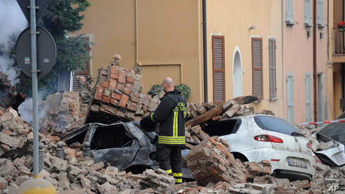 An Italian firefighter stands among rubble and destroyed cars in Modena, Italy, May 20, 2012.