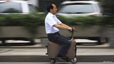 He Liang rides his home-made suitcase vehicle along a street in Changsha, Hunan province, China, May 28, 2014. He spent 10 years modifying the suitcase into a motor-driven vehicle. The suitcase has a top speed of up to 20km/h and the power capacity to ...