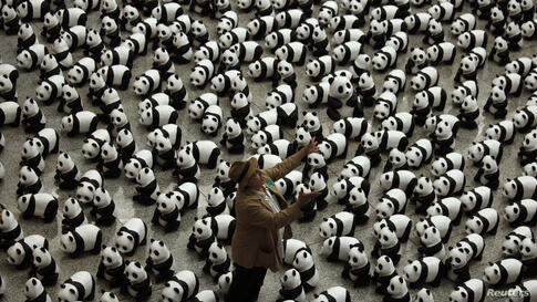"""French artist Paulo Grangeon throws one of his papier-mache pandas displayed at the arrival hall of the Hong Kong airport. The installation arrived in the city, launching the month-long """"1,600 Pandas World Tour in Hong Kong: Creativity Meets Conservati..."""