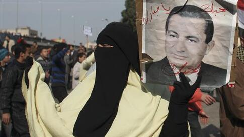 A  pro-government supporter holds a portrait of Egyptian President Hosni Mubarak in Cairo, Egypt, Wednesday, Feb.2, 2011. Several thousand supporters of President Hosni Mubarak, including some riding horses and camels and wielding whips, clashed with anti