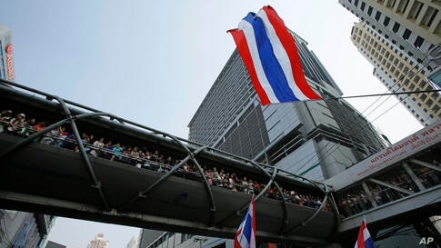 Hundreds of supporters wait for a glimpse of anti-government protest leader Suthep Thaugsuban during a march through central Bangkok, Thailand, Jan. 25, 2014.