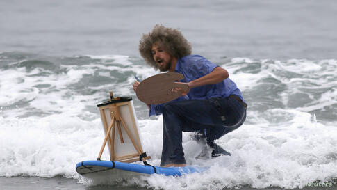 David Nickerson, 28, competes dressed as artist Bob Ross during the ZJ Boarding House Halloween Surf Contest in Santa Monica, California, Oct. 26, 2013.