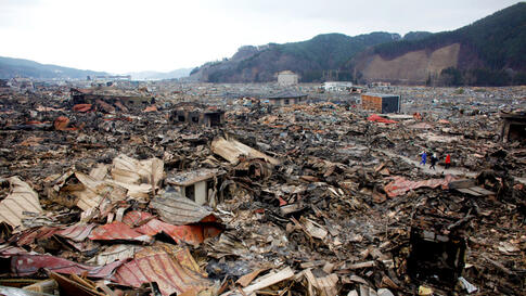 Residents walk past debris in Otsuchi March 15. 12,000 out of a population of 15,000 in the town have disappeared following Friday's massive earthquake and tsunami. (Reuters/Aly Song)