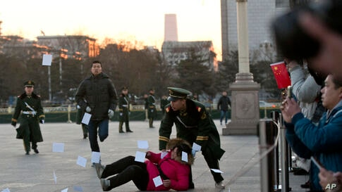 A petitioner is pushed to the ground by a paramilitary policeman after she ran into a cordoned off area near a national flag pole on Tiananmen Square and threw up flyers to protest her case of injustice, during a national flag raising ceremony early in...